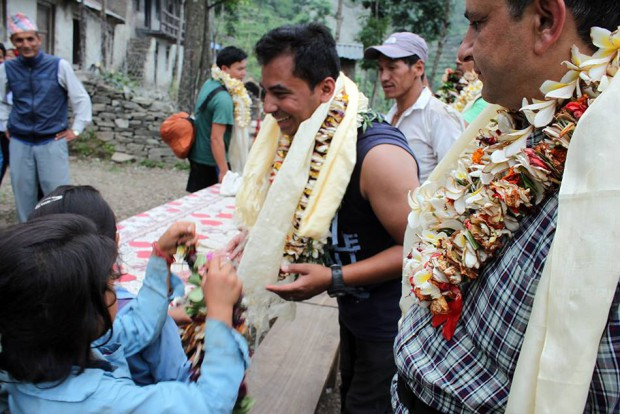 Saran is being greeted with katas and flower garlands